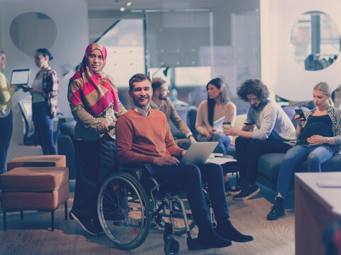 Disabled businessman in a wheelchair at work in modern open space coworking office with team