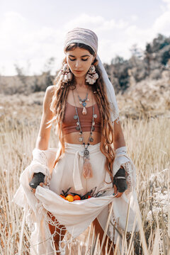 beautiful stylish young girl holding tangerines in the hem of her skirt on the field