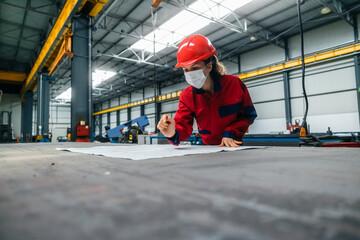 Fototapeta Female worker in safety helmet and uniform working with blueprints. obraz