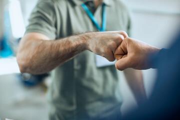 Fototapeta Close-up of auto repairmen greeting with fists at car workshop. obraz