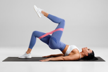 Fitness woman doing glute bridge exercise with resistance band on gray background. Athletic girl working out