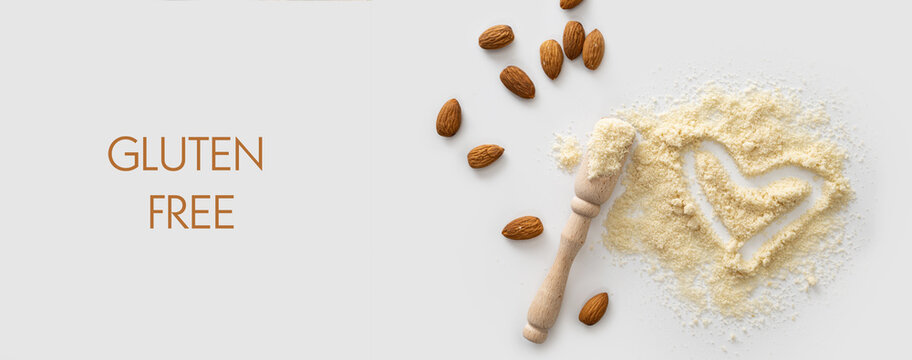 banner, almond flour with nuts scattered on white background, love heart symbol, gluten free product, keto food, top view, empty space for text