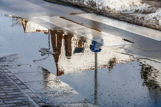 reflection of snow, a roof top and traffic signs  in a puddle