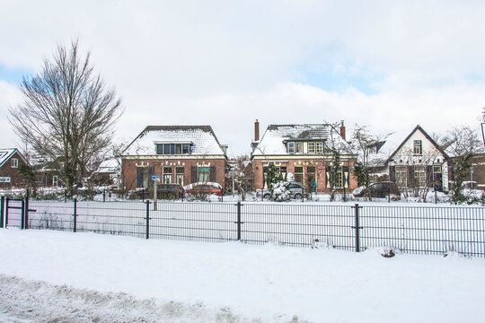 a row of old houses behind a fence in the snow in the town of Doetinchem