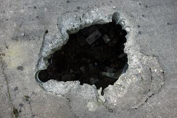 Large dark hole in the concrete floor.