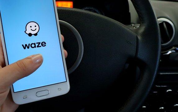 Bahia, Brazil. September 18, 2020: Woman's hand holding smartphone with Waze app on screen, inside a car. Waze is a navigation and live traffic app.