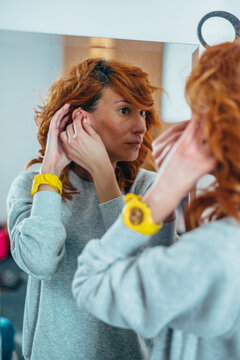 Redhead woman putting a hearing aid in her ear