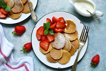 Delicious tiny pancakes with fresh strawberry. Top view with copy space.