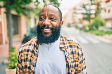 Handsome modern african american man with beard smiling positive standing at the street