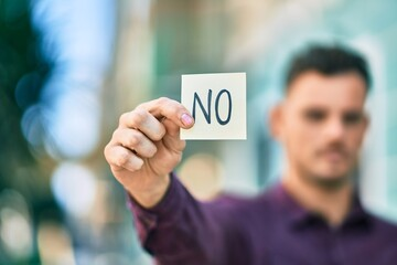 Obraz Young hispanic man with serious expression holding no reminder paper at the city. - fototapety do salonu