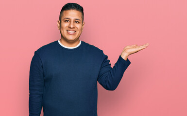 Young latin man wearing casual clothes smiling cheerful presenting and pointing with palm of hand looking at the camera.