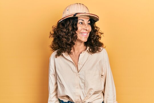 Middle age hispanic woman wearing explorer hat looking away to side with smile on face, natural expression. laughing confident.