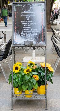 Carta de helados sobre una jardinera con flores amarillas