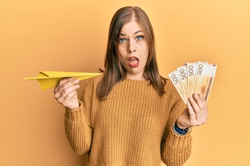 Beautiful caucasian woman holding paper airplane and 500 norwegian krone in shock face, looking skeptical and sarcastic, surprised with open mouth