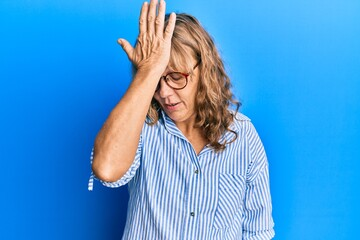 Middle age blonde woman wearing casual clothes and glasses surprised with hand on head for mistake, remember error. forgot, bad memory concept. Wall mural
