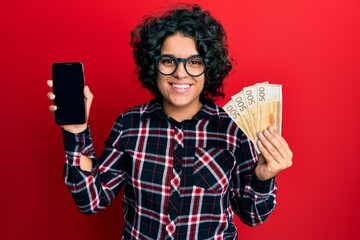Young hispanic woman with curly hair showing smartphone screen holding 500 norwegian banknotes smiling with a happy and cool smile on face. showing teeth.