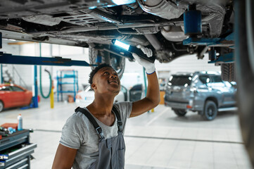 Obraz Male mechanic checks car suspension, auto service - fototapety do salonu