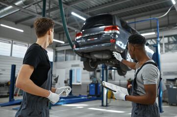 Obraz Two male mechanics talking in car service - fototapety do salonu