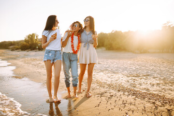 Fototapeta Three young woman spending time together at the beach, having picnic, eating pizza. Fast food concept. Beach holiday and summer vacation concept. obraz
