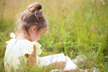 Girl in a yellow dress sits in the grass on a blanket in a field and reads a paper book. International Children's Day. Summer time, childhood, education and entertainment, cottage core. Copy space