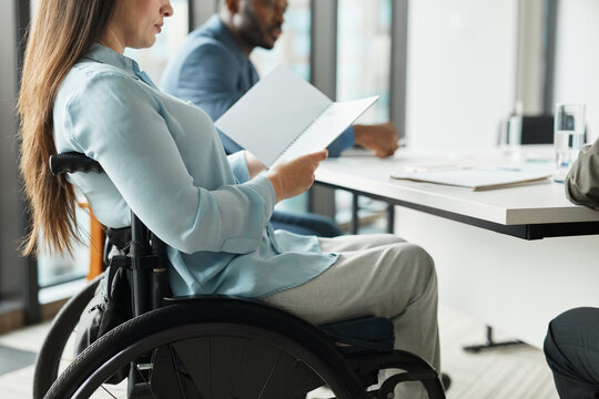 Cropped side view portrait of successful businesswoman in wheelchair reading documents at meeting table in office, copy space