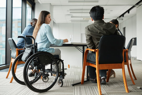 Full length portrait of successful disabled businesswoman leading meeting with diverse business team in office