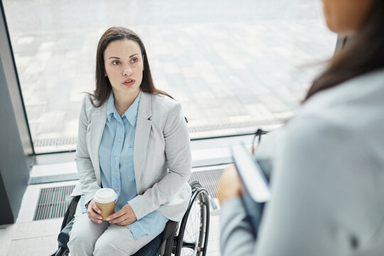 High angle view at young businesswoman in wheelchair chatting with female colleague in office lobby, copy space