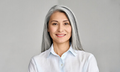 Obraz Happy smiling stylish confident 50 years old Asian female professional standing looking at camera at gray background. Portrait of sophisticated grey hair woman advertising products and services. - fototapety do salonu