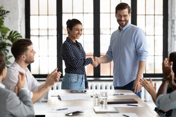 Fototapeta Happy Indian female team leader shaking hands with proud employee, thanking promoted worker for good job and congratulating with reward. Millennial business group welcoming newcomer with applause obraz