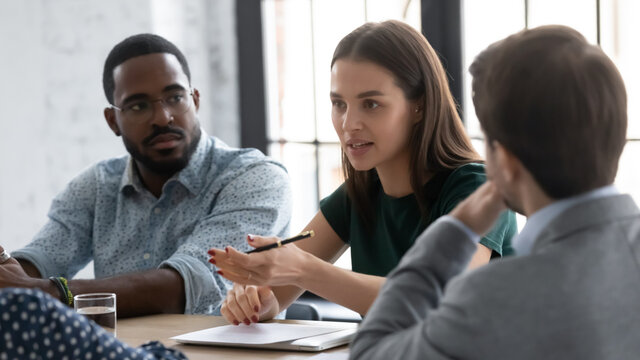Millennial team of interns or employees brainstorming at business training set, discussing project tasks. Young female manager speaking and sharing ideas with colleagues, reviewing sales report