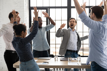 Fototapeta Happy excited millennial employees shouting for joy, raising hands for emotional high fives. Business team of overjoyed professionals cheering, celebrating good sales result, financial goal achieving obraz
