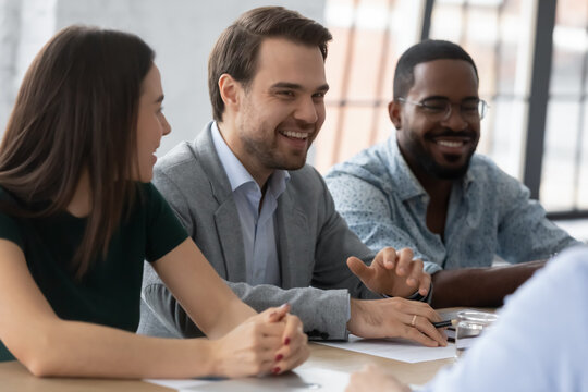 Multiethnic employer HR managers team smiling and laughing on job interview in office, sitting at meeting table together, talking to employee candidate. Professionals giving consultation to client.