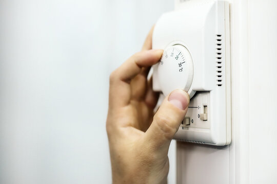 Human hand on the air conditioner temperature controller. Service for the installation and configuration of climate equipment.