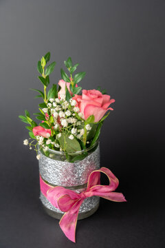 Small vase with pink bow and rose flowers, black background with copy space