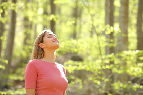 Woman breathing fresh air in a beauty forest