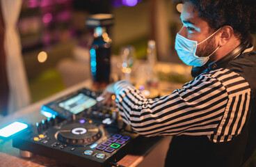 Fototapeta African dj mixing music at cocktail bar while wearing face safety mask during coronavirus outbreak - Entertainment, social distance and party concept - Soft focus on his ear obraz