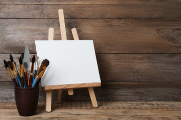 Fototapeta Easel with blank canvas and brushes on wooden table. Space for text obraz