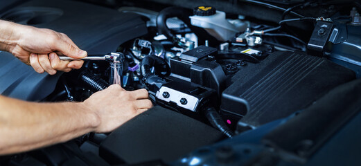 mechanic working with wrench on vehicle engine in car service. maintenance and repair. banner copy space