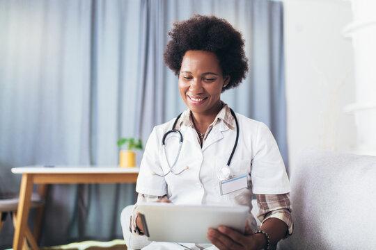 Portrait of happy black healthcare worker using digital tablet.
