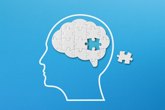 Brain shaped white jigsaw puzzle on blue background, a missing piece of the brain puzzle, mental health and problems with memory