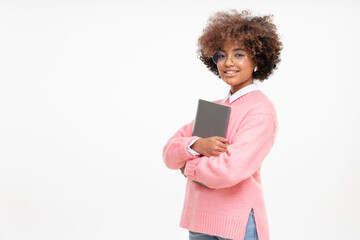 Fototapeta Portrait of african american teen girl, high school or online course student holding closed laptop, isolated on gray background obraz