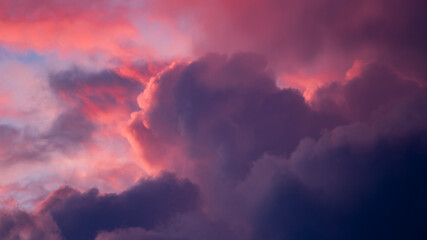 Magenta and blue contrasting intense vibrant dramatic cloudscape scenery with clouds lit up in various shades against blazing sunset. Climate and weather condition backdrop concept. Wallpaper. - fototapety na wymiar