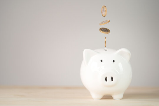 Coins falling and dropping to white piggy bank saving ,money saving for investment and retirement in the future concept.