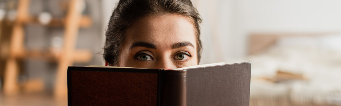 woman obscuring face while holding book and looking at camera, banner