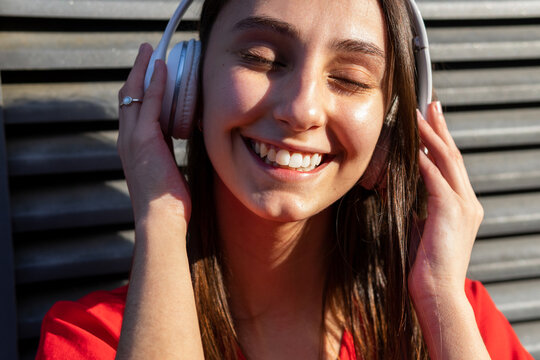 Crop cheerful female with closed eyes listening to song from headset on gray background in sunlight
