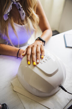 Crop anonymous female putting hands into UV nail lamp dryer for gel polish after manicure