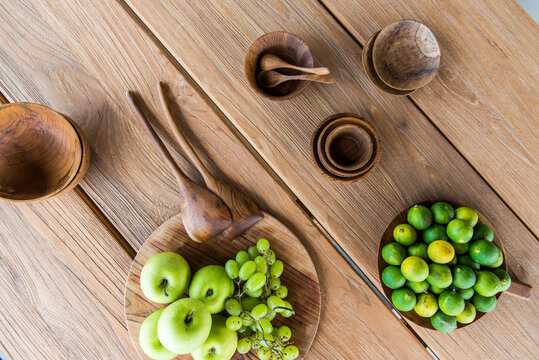 Top view of fresh ripe green apples with grapes placed on wooden tray near plate of limes and various traditional bowls served on table in sunlight