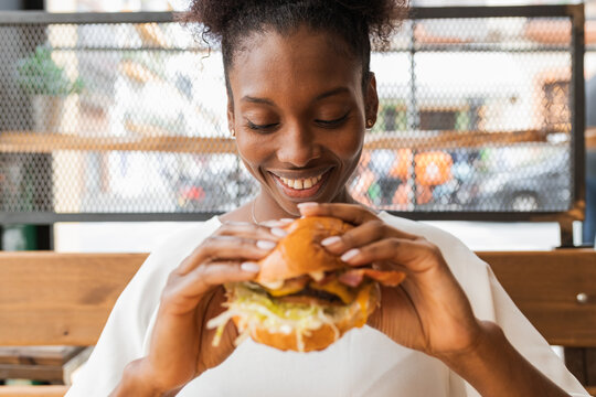 Crop African American female in casual wear eating delicious fresh cheeseburger in light room