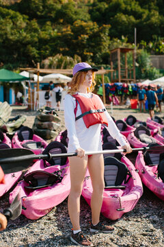 Full length serious young female in life jacket and cap holding paddle while standing on coast near many kayaks on sunny day in Malaga Spain