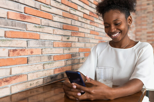 Cheerful young African American female in white shirt browsing mobile phone while sitting at table with cold drink in restaurant